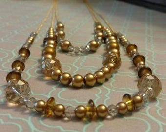 Gold-beaded multi-strand necklace with bonus earring set