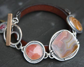 laguna lace agate, agua nueva agate, ruby, leather, and sterling silver metalwork link toggle bracelet