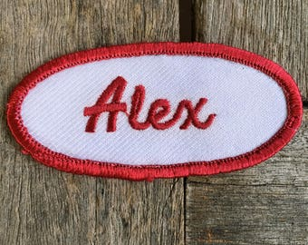 "Alex. A white work shirt patch that says ""Alex"" in red script with red border"
