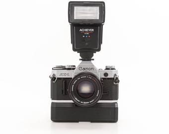 Canon AE-1 35mm Film Camera with 50mm Prime Lens Achiever Flash Arkon Power Winder and 1 Roll Film - Working Condition