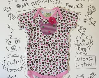 pink leopard baby onesie with kitty face appliqué