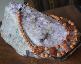 Carved wooden bean choker.