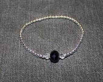 Simple silver bracelet with a deep blue rondelle faceted gem