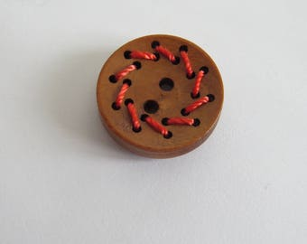 Round wood button with red thread
