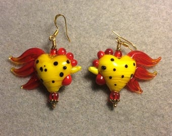 Yellow and red heart shaped lampwork rooster bead earrings adorned with red Czech glass beads.