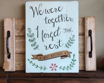"""Wooden sign with """"We were together. I forget the rest"""" quote by Walt Whitman."""