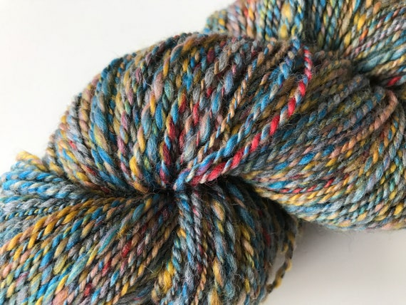 Sportweight hand spun yarn with BFL and Merino wool mix in blue, red, yellow and grey.