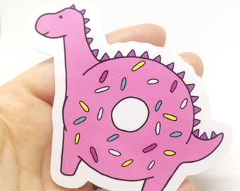 Donutosaur vinyl sticker. Cute pink donut dinosaur sticker. Doughnut and dino combo with sprinkles