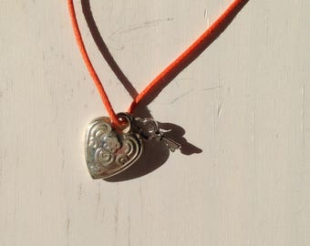 Orange heart and silver charms on a cord necklace
