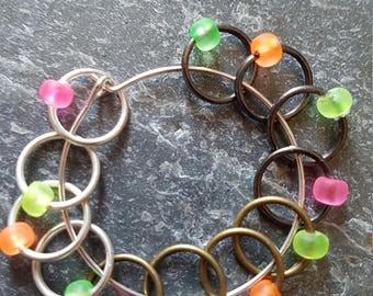 12 medium sized snag free ring style knitting stitch markers  . Fluorescent and metals