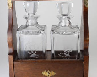 Oak two decanter tantalus with brass mounts & handle,
