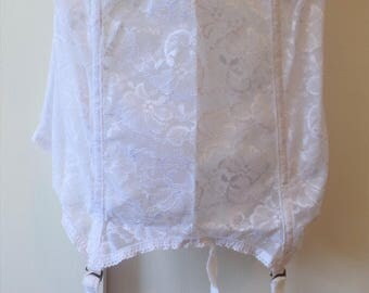 A vintage size 36D white wedding bustier made by Goddess with the original garters