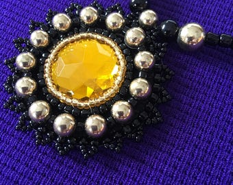 Gold and black bead embroidered necklace.