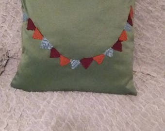green square cushion cover with garland across the front 20x20