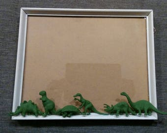 Vintage frame with green dinosaurs, white wood