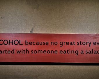 Alcohol because no great story ever started with someone eating a salad wooden sign