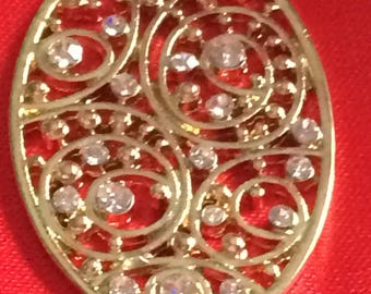 Oval Embellishment with Little Diamonds going around the inside.