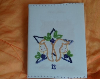 photo album covered in fabric with embroidered Gemini sign bead