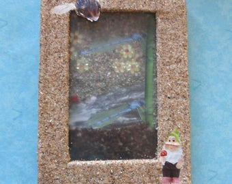 cardboard frame and sand-colored dragonfly, bee and the dwarf