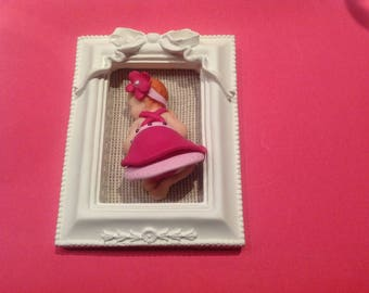 baby polymer clay in a white frame decorated with a bow