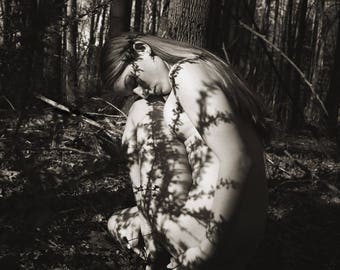 Long Shadows (Mature) - Fine art black and white photography print, crouched female nude in forest with shadows on skin