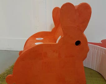 Orange rabbit sits