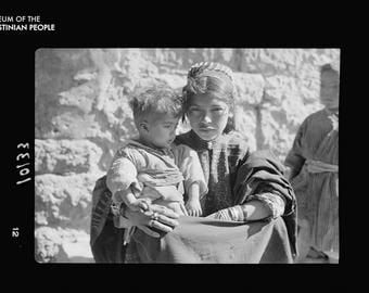 Close Up - Young Bethlehem woman holding a child