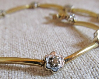 14K gold bracelet with 2mm round brilliant cut diamonds two-toned with nine white gold flower stations