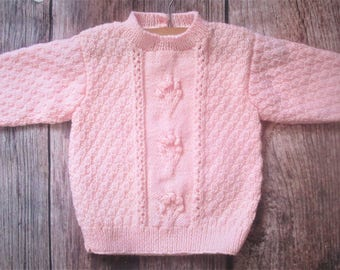 Little young baby girl's pastel pale pink patterned handknitted textured sweater jumper with flower cluster detail