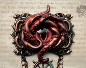 Framed Kraken eye brooch in copper & red with ship's helm and chains // Polymer clay, glass + brass // Steampunk Nautical Fantasy jewellery