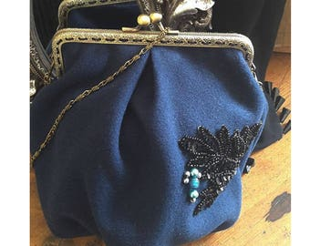 Bag with metal clasp and hand embroidery detail