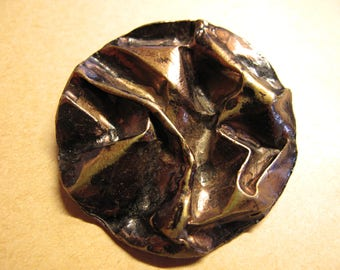 1  Black & copper 1890's metal button has a creased material look  50 mm diameter 050617/1