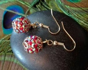 Golden color reflection/red rhinestone earrings.