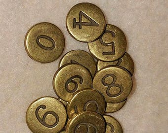 tiny brass circles with a number on each one. burnished brass, 3/8 inch