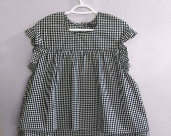 Chequered black and white top, ruffled sleeves and pleats in the center