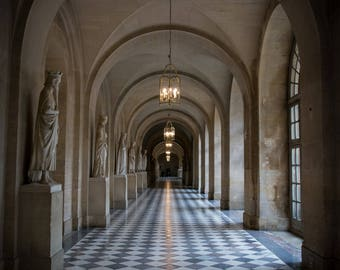 Photograph: corridor lined with marble statues in the Palace of Versailles