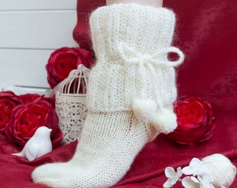 Handmade knitted socks, made of a lush cuff of mohair and rope, form cute pom-poms.