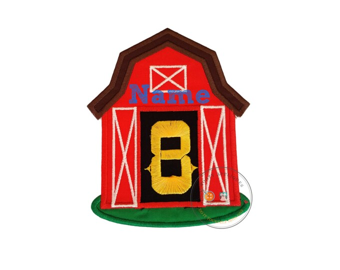Big, red barn iron-on applique with yellow, birthday number 8 between two, white embroidered doors and black background beneath a brown roof