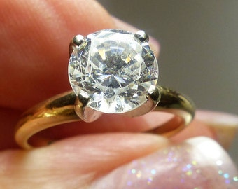 14kt gold ring with CZ stone (Hallmarked) 2 grms- sz 5- 7mm diameter stone- prongs stand 7mm high. 1984