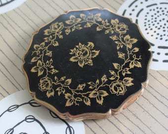 Black & Gold Rose Powder Compact By Stratton of England. Presented in with Organza Bag.