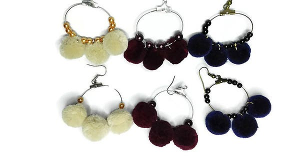 Metal hoop earrings with statement pom poms and beaded details by GunaDesign