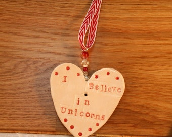 I Believe in Unicorns Pottery Ornament. Hand painted with lovely white and red glazes. Sent to you in a white gossamer bag.