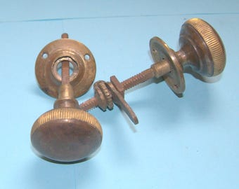 A pair of period brass cupboard door knobs with catch