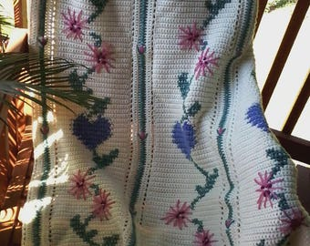 Crocheted afghan with hearts and flowers