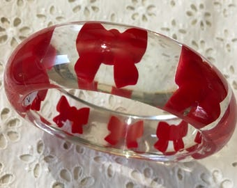 Clear acrylic bangle with red bows