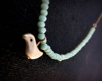 Necklace asymmetrical bird brass and green faceted beads of water