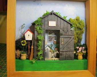 Garden shed diorama in square unpainted wood frame
