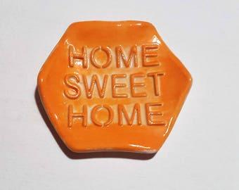 """Home sweet home"" ceramic tea bag rests bright neon orange"