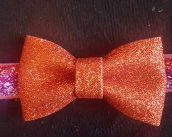 Red glitter bow on a red and purple ombre headband