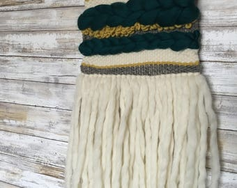 dark teal, mustard yellow, white, and grey hand woven wall hanging